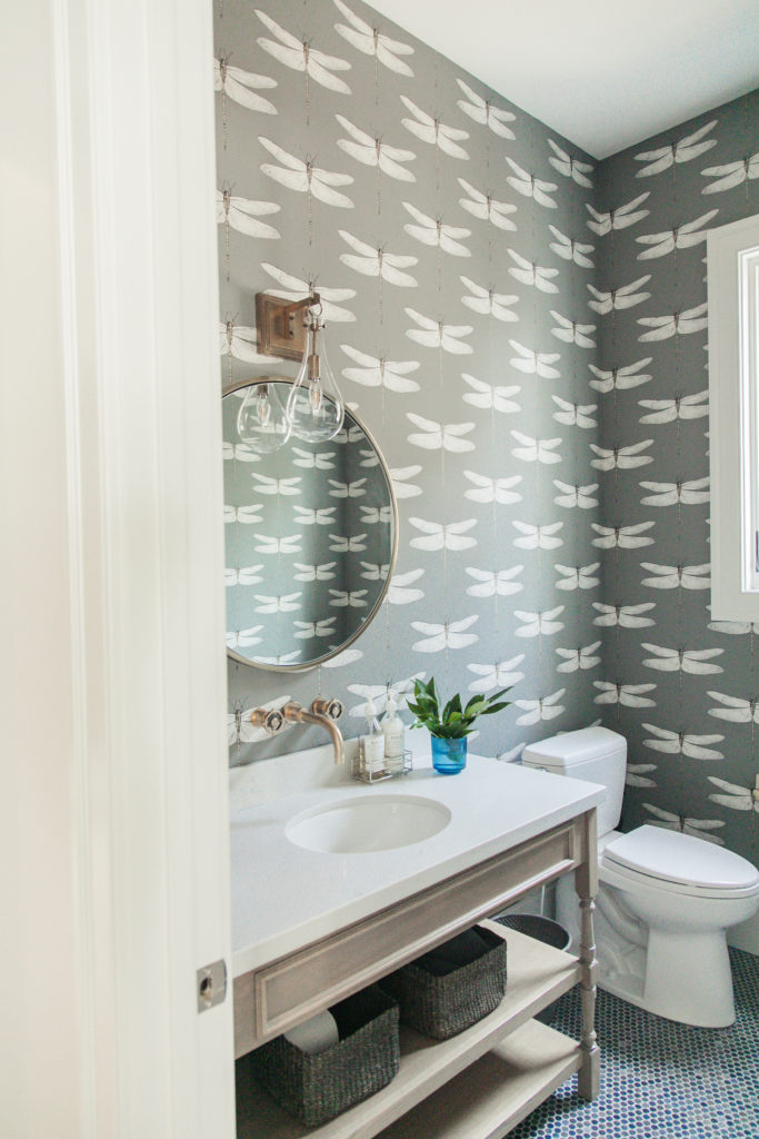 shop this pretty powder bath space! Love the lighting and faucet and fun wallpaper